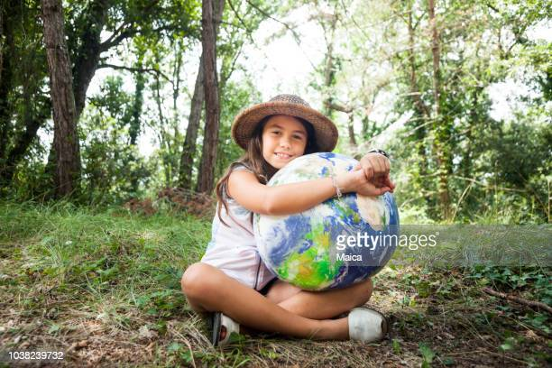little girl embracing world globe - giornata mondiale della terra foto e immagini stock