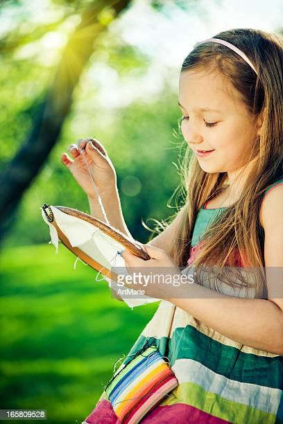 Kleines Mädchen embroidering im Freien