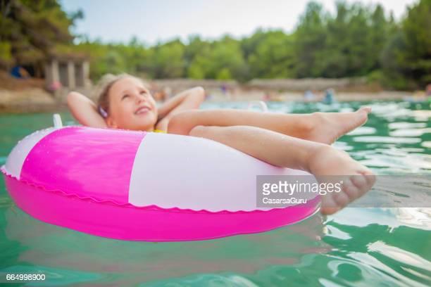 Little Girl Enjoy Beach Holiday On Swimming Tube