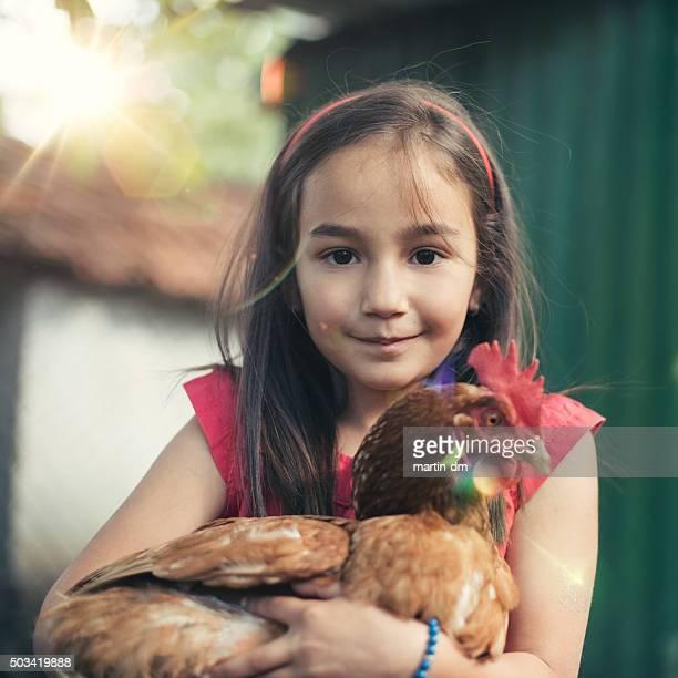 Little girl enjoying a brown hen