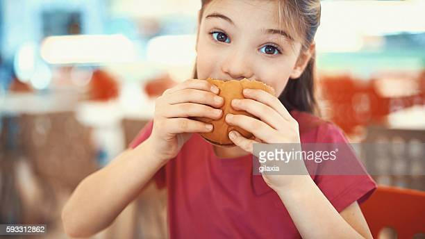 Little girl enjoying a burger.