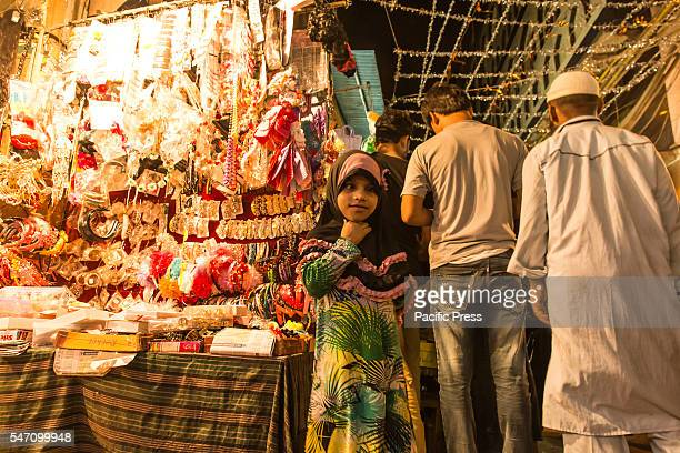 Little girl enjoying artificial Jewelery shopping in a street shop in the last night of the concluding day of Eid-ul-Fitr at Delhi. Eid-ul-Fitr,...