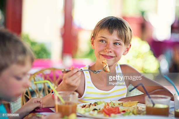 Little girl enjoying dinner in restaurant with family