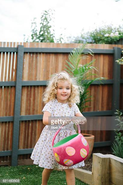 little girl enjoying easter egg hunt - ippei naoi stock photos and pictures