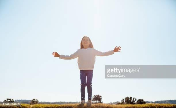 little girl genießen erste frühlingssonnenstrahlen - innocence stock-fotos und bilder