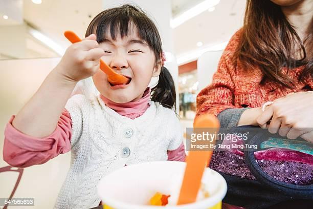 Little girl enjoying ice-cream with her mom