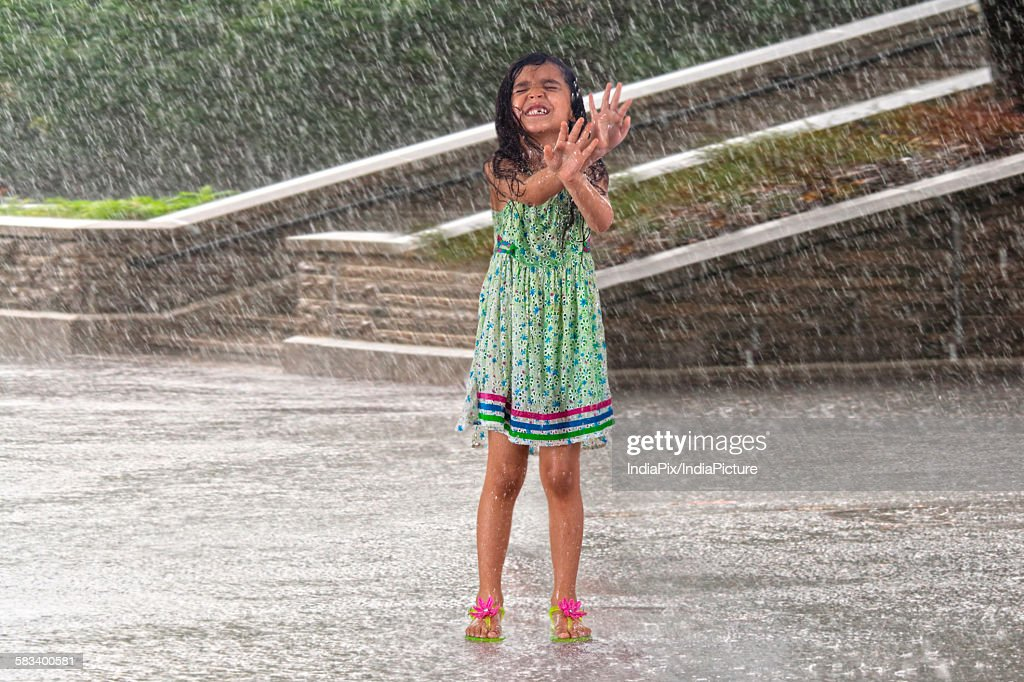 Little girl enjoying in the rain : Stock Photo