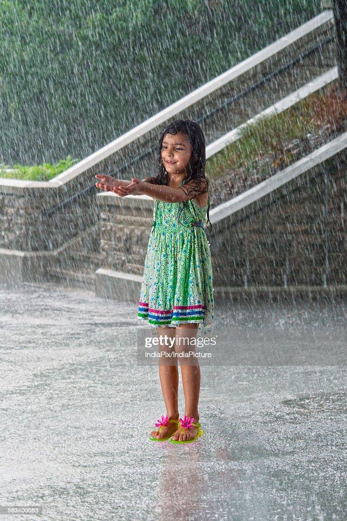 Little girl enjoying in the rain : Stock Photo