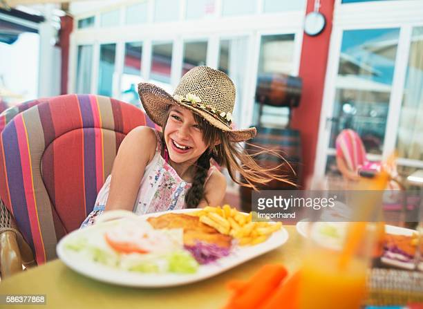 Little girl enjoying lunch in outdoors restaurant