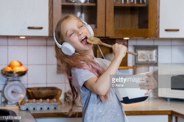 little girl enjoying music while preparing food in kitchen - singing stock pictures, royalty-free photos & images