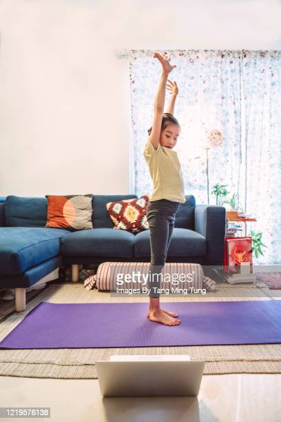 little girl enjoying online yoga class with laptop computer at home - praticare foto e immagini stock