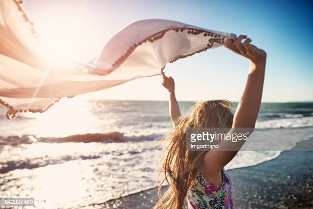 Little girl enjoying sunset on a windy beach