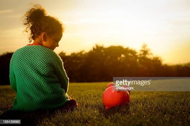 Little girl enjoying sunset with her piggy bank