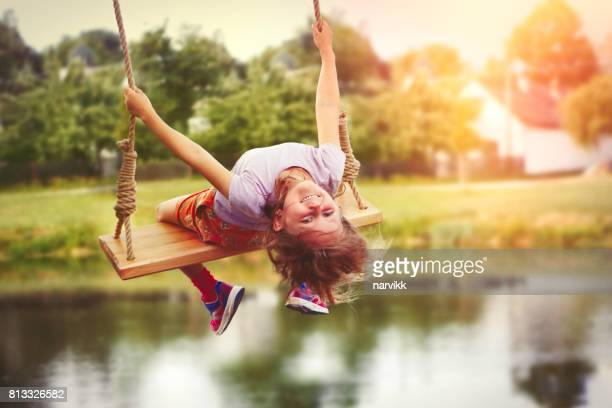 Little girl enjoying swinging in countryside