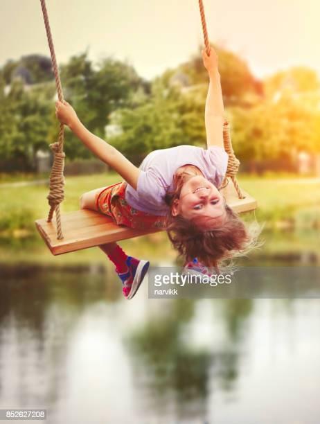 Little girl enjoying swinging in countryside