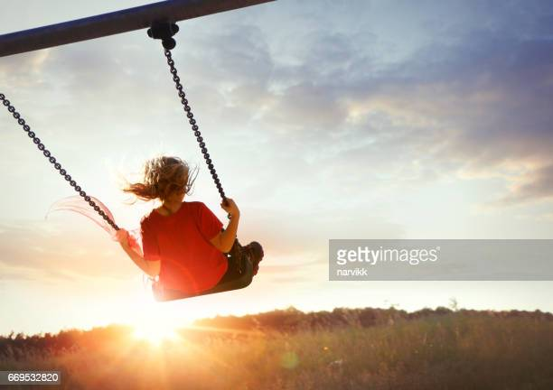 little girl enjoying swinging - coraggio foto e immagini stock