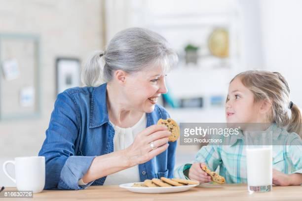 Niña disfruta las galletas y la leche con su abuela
