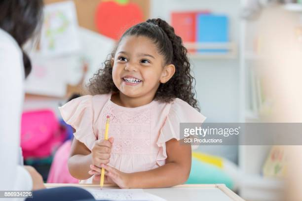 Little girl enjoys discussion with day care worker