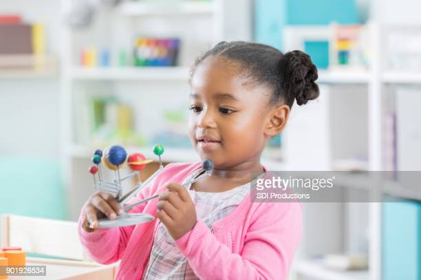 little girl enjoys examining solar system model in preschool - solar system stock photos and pictures