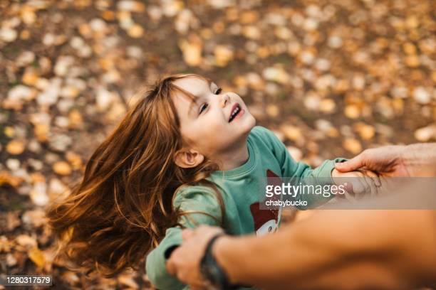 kleines mädchen genießt im herbsttag mit ihrem vater - september stock-fotos und bilder