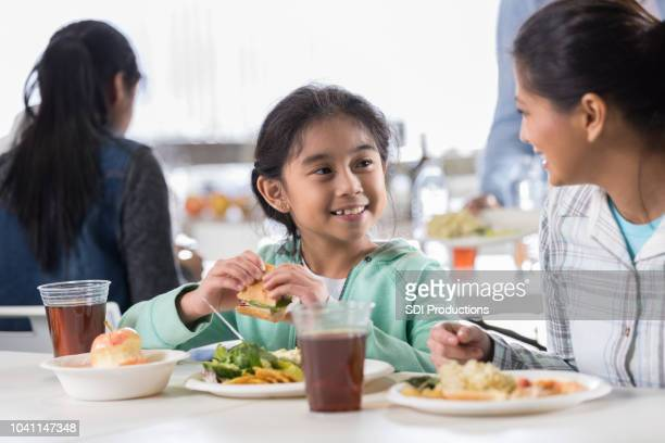 little girl enjoys soup kitchen meal with mother - homeless shelter stock pictures, royalty-free photos & images