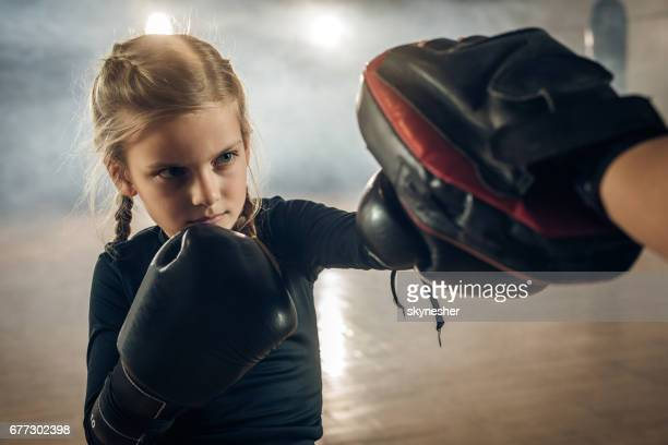 Little girl exercising boxing with unrecognizable trainer in a health club.