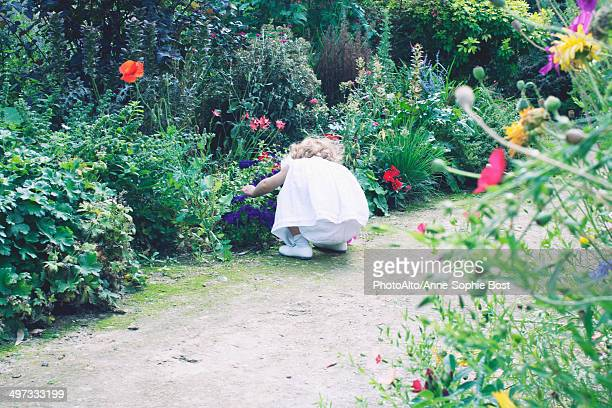 Little girl exploring flower garden