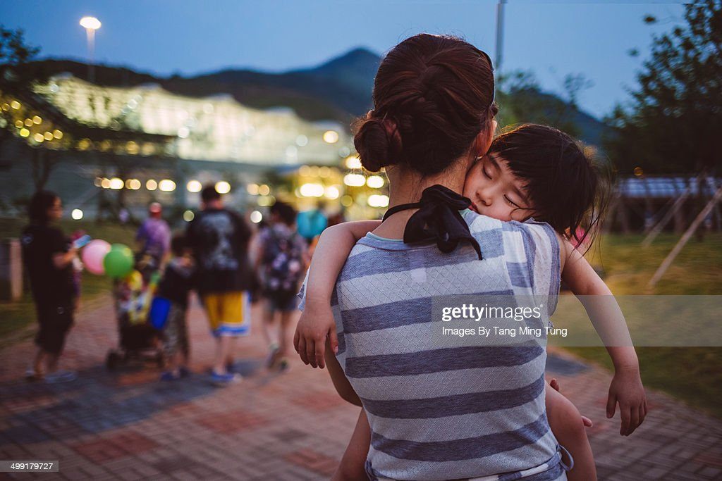 Little girl falling asleep on mom's shoulder : Stock Photo