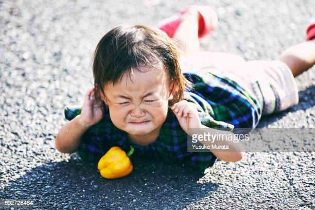 Little girl falling down and crying on the road