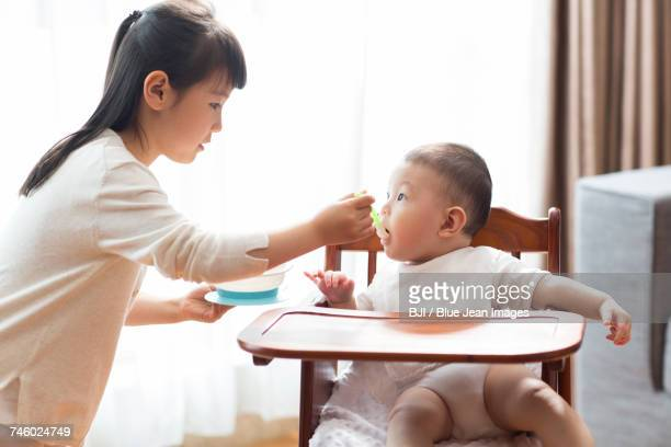 Little girl feeding baby