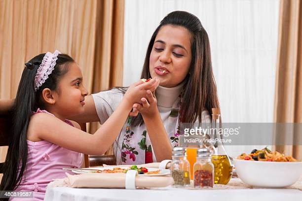 Little girl feeding pizza to mother at restaurant table
