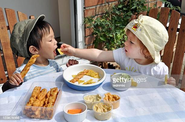 Little girl feeds little boy
