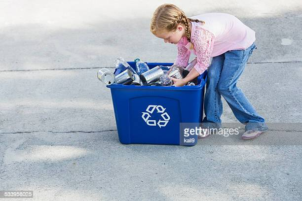 Little girl filling recycling bin with cans and bottles