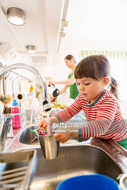 Little girl filling water in container with mother in background at kitchen counter