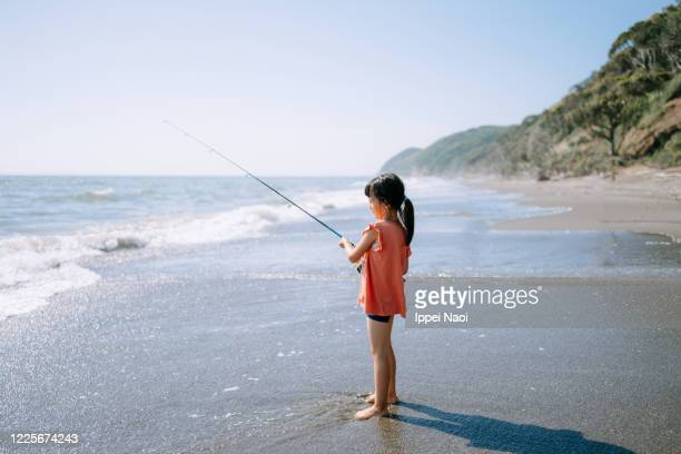 little girl fishing from beach, tokyo bay - ippei naoi stock pictures, royalty-free photos & images