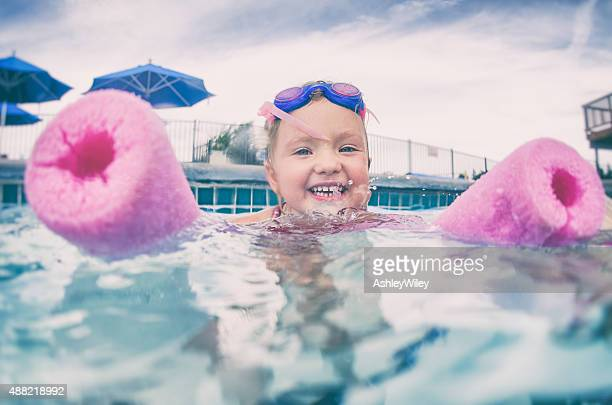 Little girl floats on the water with a swim noodle