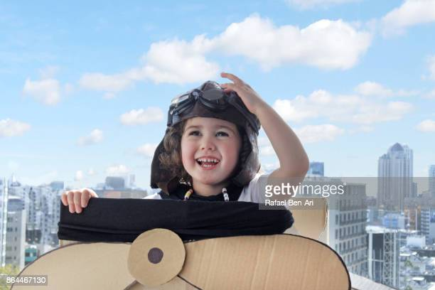 Little girl flying a cardboard airplane above city