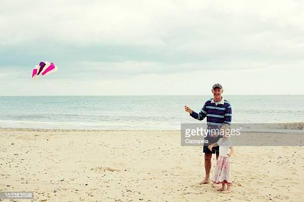 Little Girl Flying Kite with Grandad on Beach