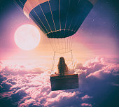 Little girl flying over the clouds