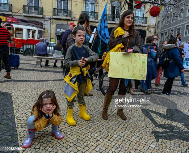 Little girl frowns and squats while demonstrating with her mother and brother at a rally in support of the climate strike on November 29, 2019 in...
