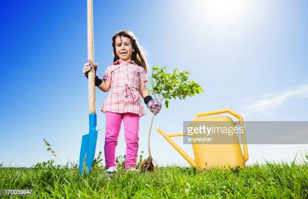 Little girl gardening on beautiful day.