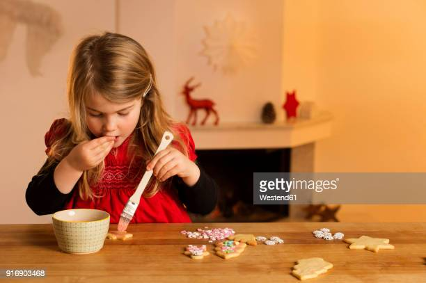Little girl garnishing Christmas cookies with hundreds and thousands