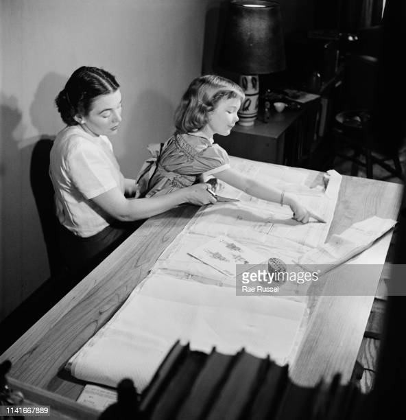 A little girl gets her dress handmade and tailored by a dressmaker at a McCall Pattern Company shop US circa 1950