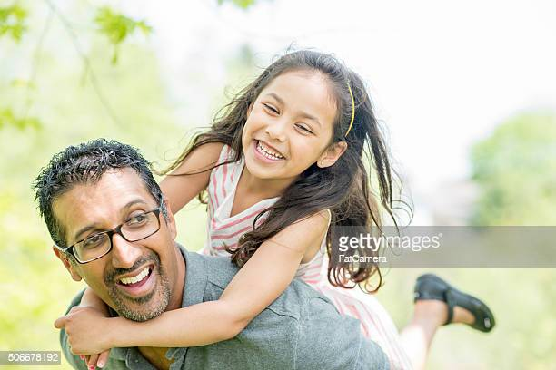 little girl getting a piggy back ride from her father - ethnicity stock pictures, royalty-free photos & images