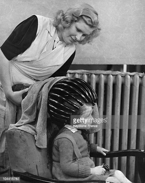 A little girl getting her hair dried thanks to a heating helmet in Berlin around 19471950