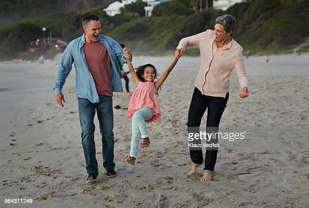 Little girl getting swinget by grandparents