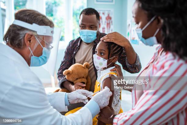 little girl getting vaccinated - diversity stock pictures, royalty-free photos & images