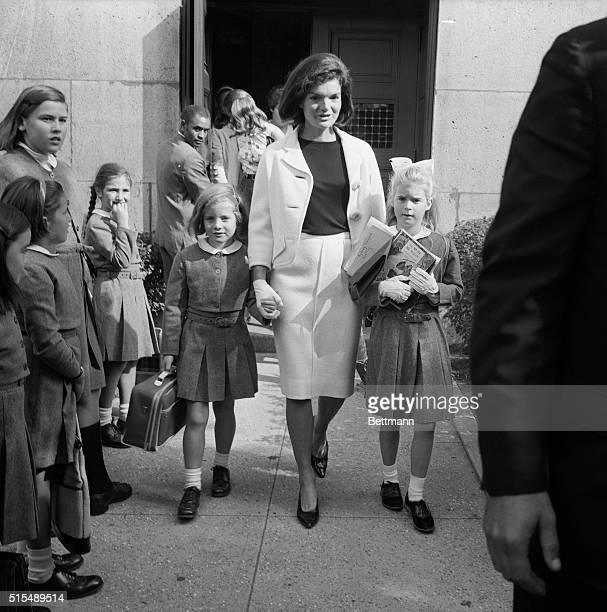 A little girl giggles as Mrs Jacqueline Kennedy picks up her daughter Caroline and her niece Sydney Lawford at the end of the school day The young...