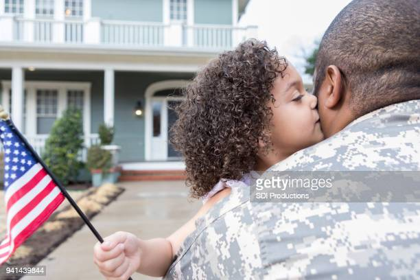 Little girl gives army dad kiss