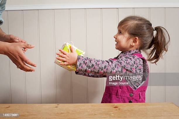 little girl giving a gift to adult - giving stock photos and pictures